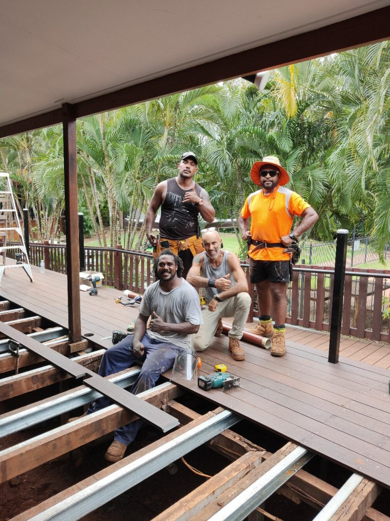 Two men stand on a deck that is in the progress of being repaired. Tropical trees are in the background. and in the foreground, two men sit around the stripped part of the deck.